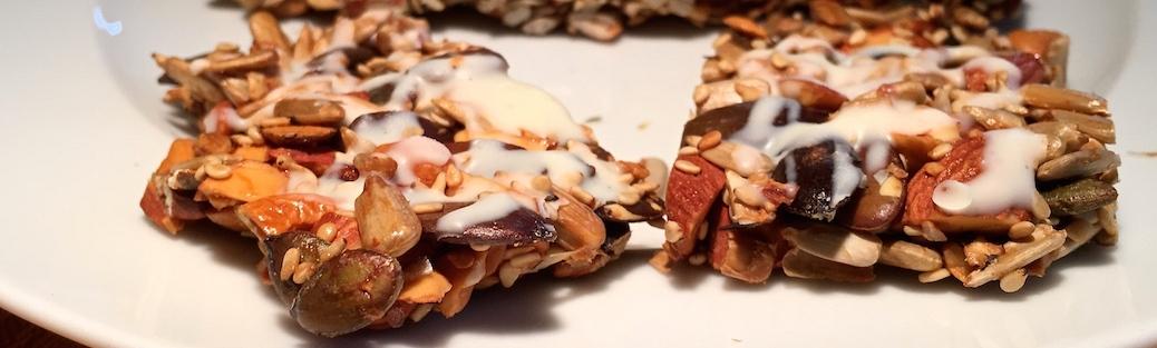 Nussriegel mit Mandeln, Sonnenblumen- und Kuerbiskernen, Sesam, Honig und weißer Schokolade